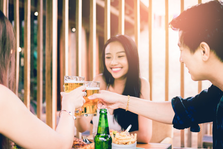 Asian people cheering beer at restaurant happy hour and laughing and talking together. Stock fotó