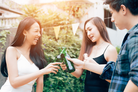 Outdoor party group of happy friends toasting with beer bottles at the garden home. Stock Photo