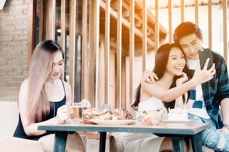 Asian single woman envious with love couple doing take selfie at restaurant. Foto de archivo
