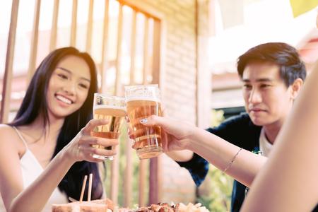 Grupo de jóvenes amigos bebiendo cerveza en el restaurante después del trabajo. Foto de archivo