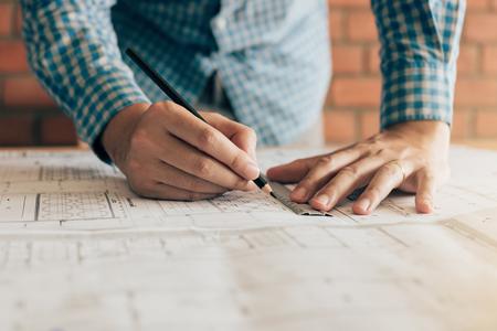 Ciérrese encima del examen de funcionamiento del hombre de la ingeniería de la mano que trabaja en un modelo para el nuevo proyecto en Ministerio del Interior.