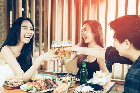 Jóvenes asiáticos que se divierten bebiendo con vítores con cerveza en el restaurante. Foto de archivo