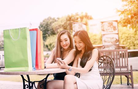 Dos mujeres asiáticas sentado en el café de la tienda con feliz viendo smartphone en centro comercial.