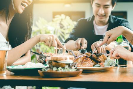 Amigos asiáticos disfrutando de comer Turquía en el restaurante.
