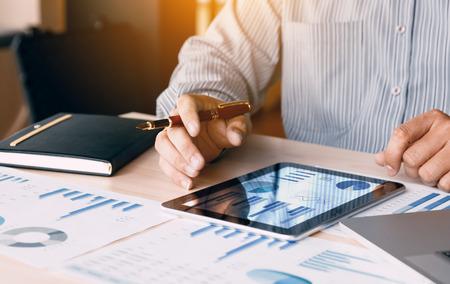 Hombre de negocios que mira el informe del gráfico y del resumen en la pantalla de la tableta digital con resultado de los datos del análisis.