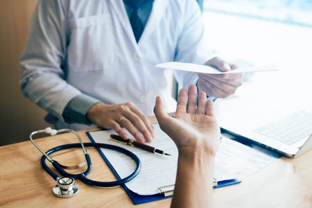 Médico de sexo masculino que le da una prescripción al paciente.