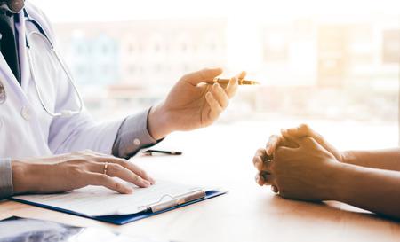 Mano del doctor que sostiene la pluma y que habla con el paciente sobre la medicación y el tratamiento. Foto de archivo