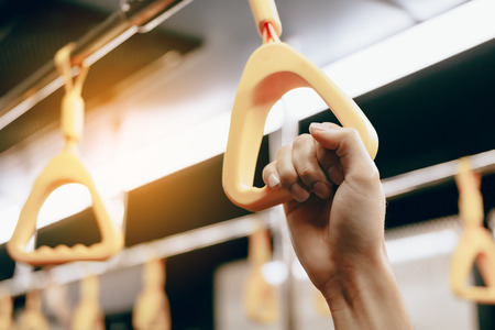Mano joven de la mujer del pasajero que sostiene la barandilla en subterráneo.
