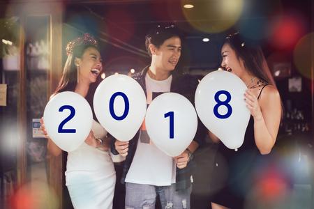 El grupo de jóvenes asiáticos que sostienen el globo numera 2018, concepto del Año Nuevo de la celebración. Foto de archivo