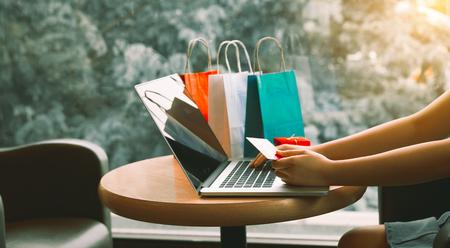 Mujer que usa la tarjeta de crédito con concepto en línea de compras en el café. Foto de archivo