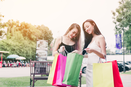 Beautiful asian female friends standing and looking in paper bag at outdoors shopping mall center retail in the city.