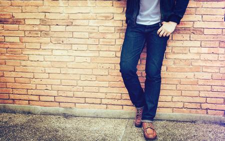 Hombre inteligente de pie frente a un fondo de pared. Foto de archivo
