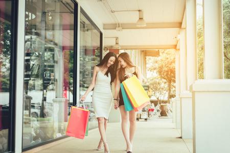 Amigos asiáticos felices que caminan y que hacen compras juntas afuera en el centro comercial.