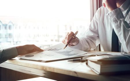 Asesor financiero que presenta informe del documento del gráfico y discusión sobre planing al cliente.