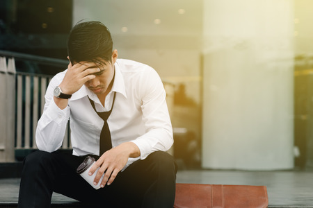 Asian man sits on the steps of an office building with stress and distraught.