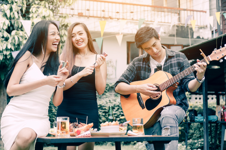 Asian young women holding paper shoot with guy playing guitar singing at home garden outdoors.