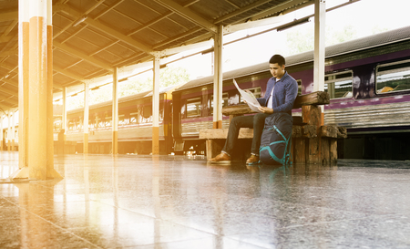 Man sitting at train station and looking on map for travel planning.