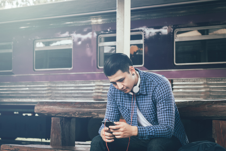 Young asian hipster man holding mobile phone using app song with linten music at train station.