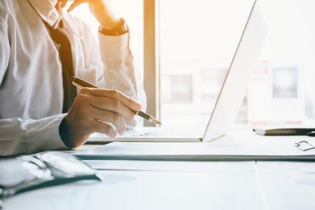 Haga hincapié en el hombre de negocios en la habitación de la oficina que sostiene la pluma que señala el gráfico del informe resumido y analice con el uso de la computadora portátil para buscar datos de información. Foto de archivo