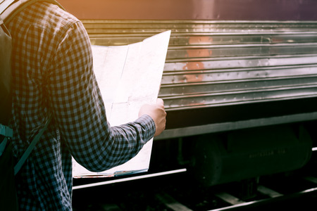 Rear view of hipster man standing on train station with looking map paper.