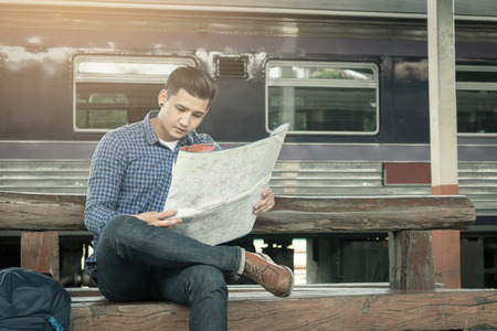 Traveler man sitting at train station and looking on map for travel planning.