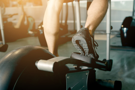 Man running in a gym on a treadmill for exercising.