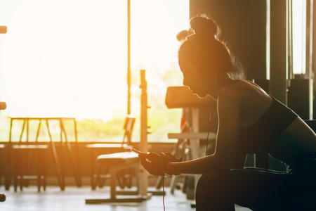 Healthy woman relaxing after exercise and  listen music after the workout.