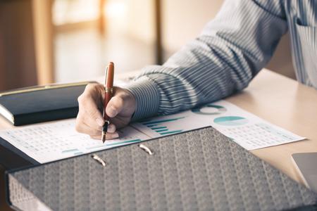 Businessman writing make note on paperwork chart summary report graph on desk for analyze data. Foto de archivo