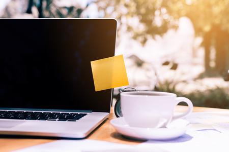 Pasta pegajosa del cojín de nota en la computadora portátil con la taza de café en el escritorio de madera.