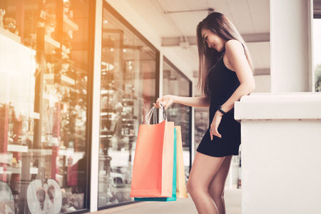 Asian young woman shopping in the outlet mall with carrying paper bags. Foto de archivo