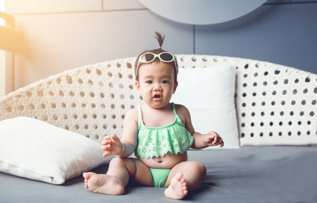 Smiling little infant girl sitting wearing swimsuit on chair in hotel.