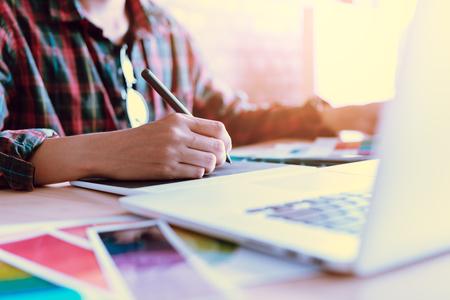 Desenhadores criativos autônomos que trabalham na mesa usando a tabuleta gráfica digital e tirando com a pena no escritório domiciliário moderno.
