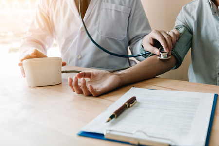Doctor checking a senior patient's blood pressure in office room.