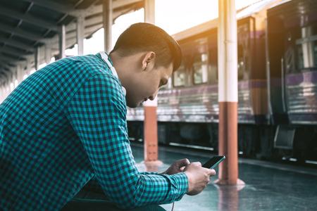 Achtermening van de jonge Aziatische hipstermens die mobiele telefoon houden die app lied met lintenmuziek gebruiken bij station. Stockfoto