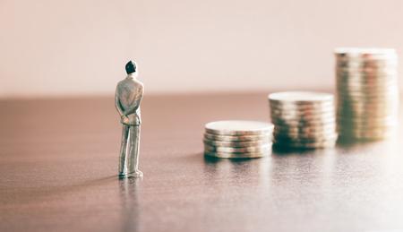 Miniaturowe ludzie szukający przyszłości z monetą stosu o koncepcji oszczędności finansowych i pieniędzy. Zdjęcie Seryjne