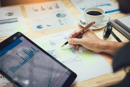 Businessman making note on sticky with looking graph in tablet.