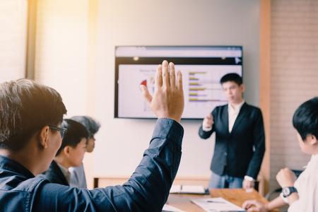 Vista trasera de un hombre de negocios que levanta la mano quiere preguntar algo en la sala de juntas. Foto de archivo