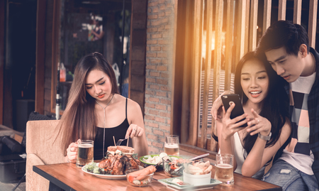 Asian single woman envious with love couple doing take selfie at restaurant. Stock fotó