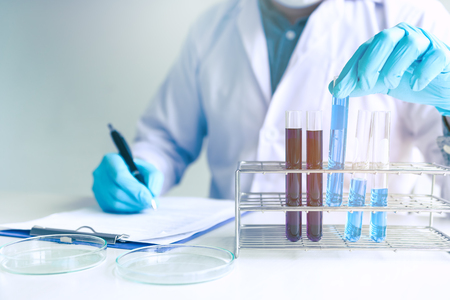 Trabajador científico masculino en bata blanca trabajando con tubos de ensayo en laboratorio.