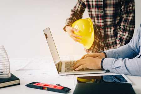 Engineer using laptop computer and working together.