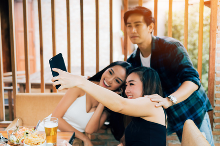 Asian friends smiling and taking selfie in restaurant. 스톡 콘텐츠