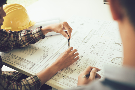 Architect working on blueprint in workplace with partnership and drawing compass. 免版税图像