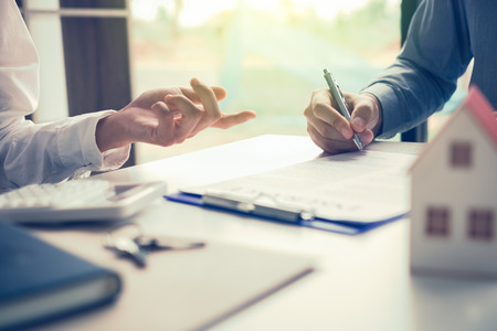 Real estate agent hand showing customer where to writing sign a contract of house or mortgage papers.