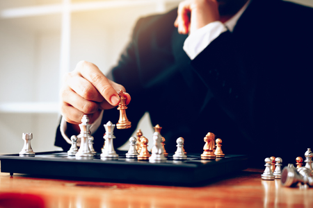 Businessman thinking about strategy concept and hand moving the king in a chess game for win. Stock Photo