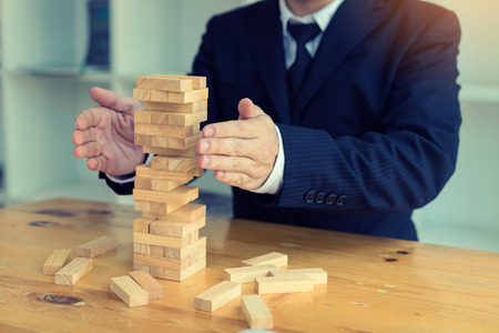 Hands of businessman protect block wooden on table with risk concept. Stock Photo