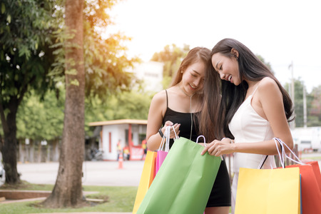 Two women are looking at a shopping bag.