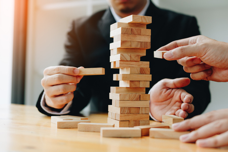 Two businessmen help to hold the wood block to fall down. Stock Photo