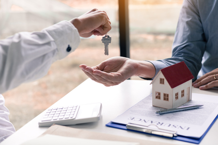 Salesman house brokers provide key to new homeowners in office. Stock Photo