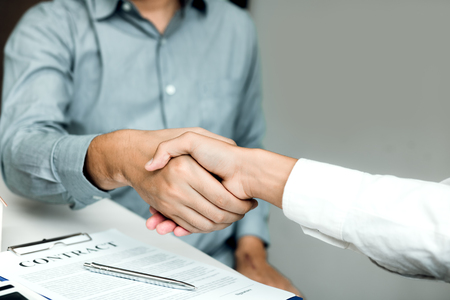 Confident partnerships people shaking hands with making a contract in the office.