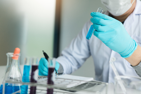 Scientist recording making note on book with his findings test tube in lab. Foto de archivo - 115915453